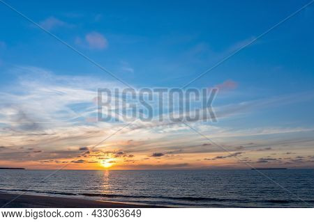 Reflection Of Sunlight In The Sea Waves. Red And Yellow Sky In The Rays Of The Sunset. Sunset Over T