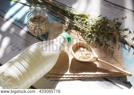 A Wooden Spoon With Oat Flakes And A Bottle Of Oat Milk On The Table With Sun Glare.