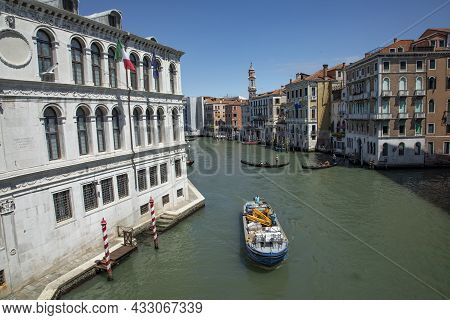 Venice, Italy - July 2, 2021: View From Rialto Bridge To Canale Grande With Ship Of A Builder In Ven