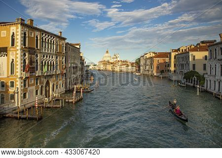 Venice, Italy - July 2, 2021: Gondola At Grand Canal With View To Old Customs House In Late Afternoo