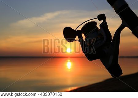 Fishing reel on a fishing rod on a sunset background over lake