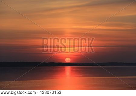 Majestic red sunset over lake water surface
