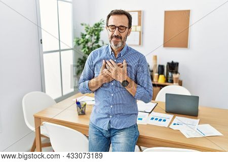 Middle age hispanic man with beard wearing business clothes at the office smiling with hands on chest with closed eyes and grateful gesture on face. health concept.