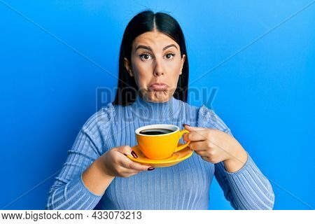 Beautiful brunette woman drinking a yellow cup of black coffee depressed and worry for distress, crying angry and afraid. sad expression.