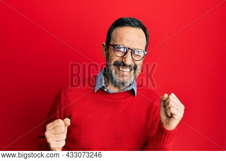 Middle age hispanic man wearing casual clothes and glasses excited for success with arms raised and eyes closed celebrating victory smiling. winner concept.