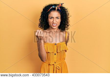 Young latin girl wearing summer dress angry and mad raising fist frustrated and furious while shouting with anger. rage and aggressive concept.
