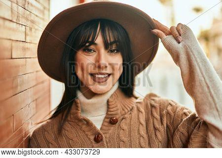 Brunette woman wearing winter hat smiling leaning on bricks wall