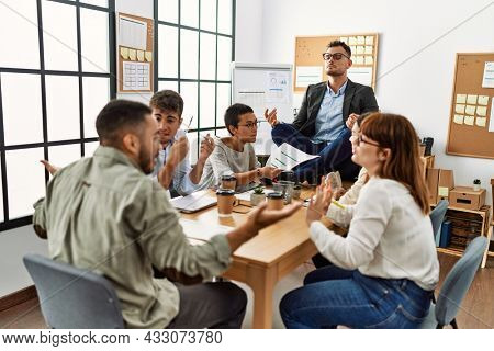 Businessman enjoys meditating during meeting. Sitting on desk near arguing partners at the office.
