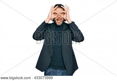 Middle age handsome man wearing business clothes doing ok gesture like binoculars sticking tongue out, eyes looking through fingers. crazy expression.