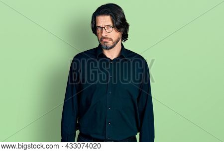 Middle age caucasian man wearing casual clothes and glasses skeptic and nervous, frowning upset because of problem. negative person.