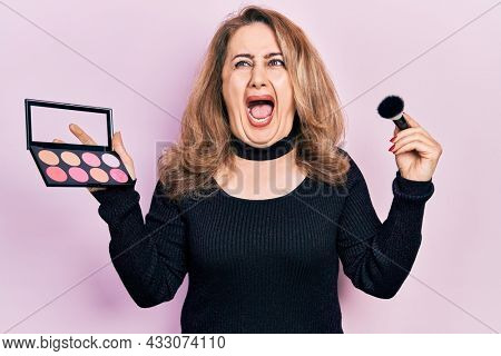 Middle age caucasian woman holding makeup brush and blush angry and mad screaming frustrated and furious, shouting with anger. rage and aggressive concept.