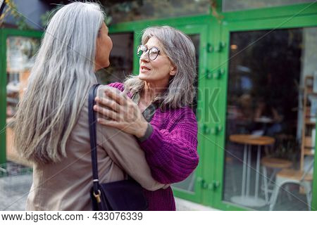 Positive Senior Lady Embraces Friend With Grey Hair Meeting On City Street