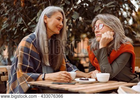 Smiling Senior Asian Woman Holds Hand Of Upset Friend Sitting Together In Street Cafe