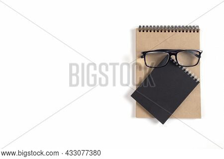 Two Notepads And Glasses Lie On White Surface. Recycled Paper Notebook As Concept Of Ecology, Recycl