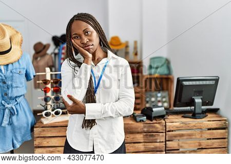 Black woman with braids working as manager at retail boutique thinking looking tired and bored with depression problems with crossed arms.