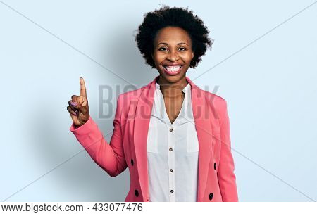 African american woman with afro hair wearing business jacket showing and pointing up with finger number one while smiling confident and happy.