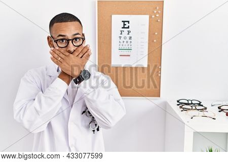 African american optician man standing by eyesight test shocked covering mouth with hands for mistake. secret concept.