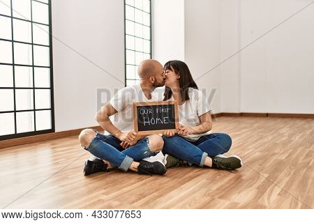 Young hispanic couple smiling happy holding our new home blackboard at empty new house.
