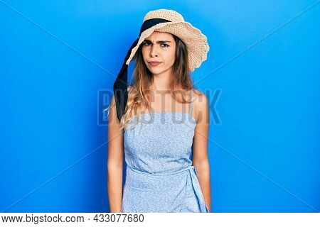 Young hispanic girl wearing summer hat skeptic and nervous, frowning upset because of problem. negative person.