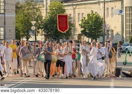 Kyiv, Ukraine - June 12, 2021: Hare Krishna devotees from International Society for Krishna Consciousness walking along the street, singing and dancing in Kiev, Ukraine.