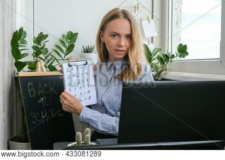 Young Female Teacher Sitting At Desk And Using Laptop Teaching Mathematics At Home. E Education Back