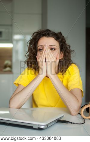 Tired Young Woman With Curly Hair And Yellow Shirt Is Working From Home Using Her Laptop At The Kitc