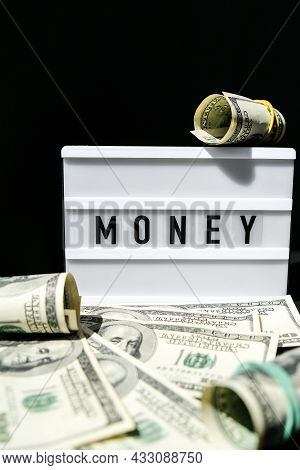 Lightbox Board With The Word Money In Black Letters Around Us Dollar Banknotes. Finance Background.