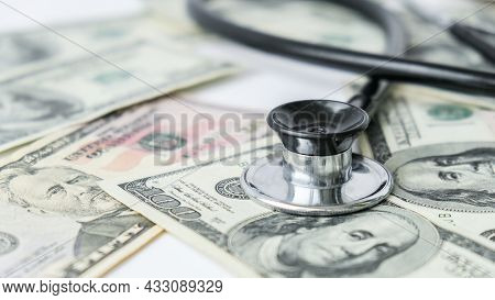 Stack Of Cash Dollars And Stethoscope. The Concept Of Medical Expensive Medicine, Doctors Salary. Co