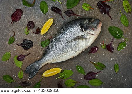 Close Up One Fresh Raw Dorada Sea Bream Fish On Table, With Lemon Wedges, And Salad Leaves, Elevated