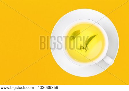 Close Up One Full White Cup Of Green Oolong Tea With Leaf On Saucer Over Yellow Background, Elevated