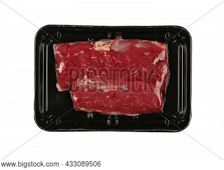 Close Up Raw Lamb Or Mutton Meat Fillet Cut Steak Vacuum Sealed With Black Plastic Film, Isolated On