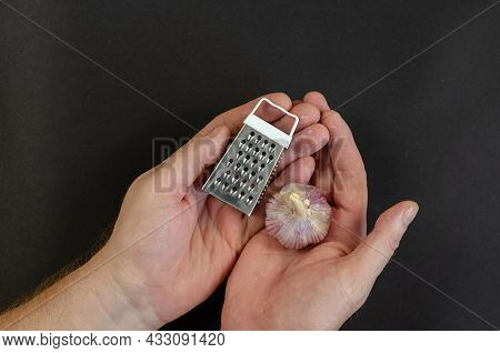 Male Calloused Hands Hold A Ripe Head Of Garlic And A Metal Grater Against A Dark Gray Background. H