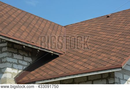 Brown Asphalt Shingled Roof Valley Leaking Problem Area With A Ventilation Cap. A Close-up Of Asphal