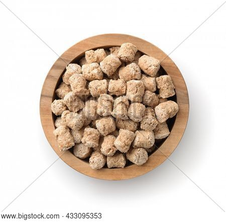 Top view of oats bran pellets in wooden bowl isolated on white