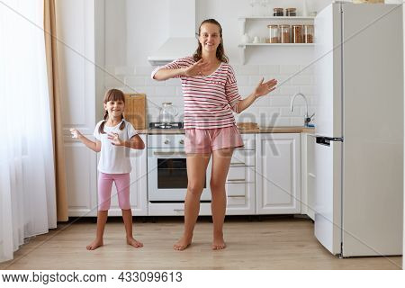 Indoor Shot Of Happy Positive Family Dancing Happily Together, Making The Same Moving, Looking Smili