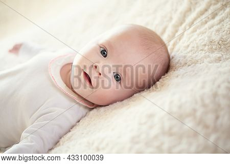 A Charming Baby In A White Sunny Bedroom. A Newborn Baby Is Resting In Bed. Childrens Room For Small