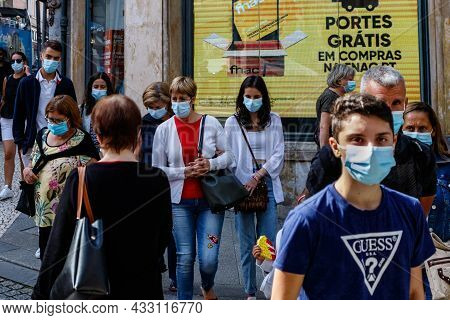 Porto, Portugal - September 11, 2021: Group Of People In Protective Masks Cross The Street In The Ce