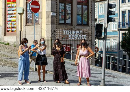 Porto, Portugal - September 11, 2021: A Group Of Women Wearing Protective Masks Cross The Street In