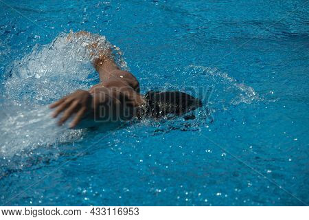 Detail Of A Young Man In Swimming Trunks Swimming With His Arms In A Swimming Pool