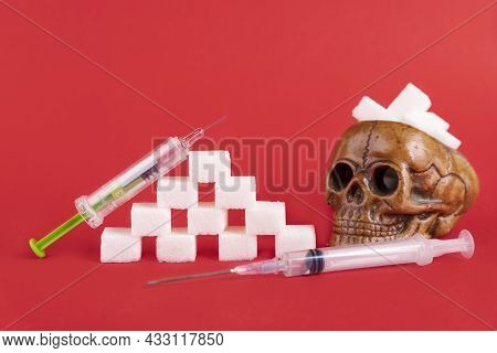 A Human Skull Filled With Cubes Of Refined White Sugar On A Red Background. Copy Space.