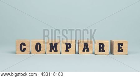 The Word Compare Made From Wooden Cubes On Blue Background. Conceptual Photo