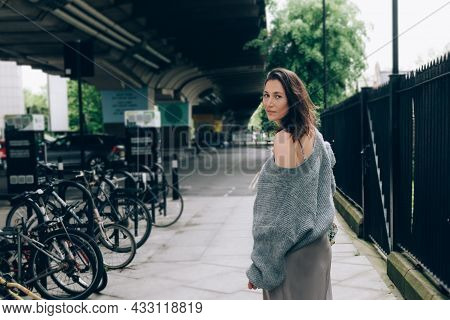 Stylish Elegant Young Woman In Trendy Grey Sweater And Silk Skirt Is Walking On London Streets With