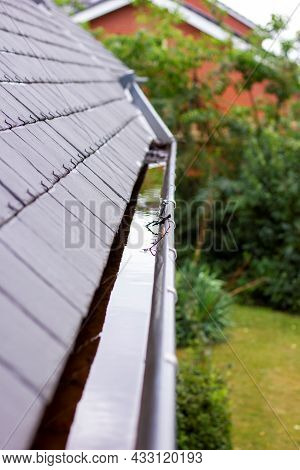 A Portrait Of A Clogged Roof Gutter Full Of Rain Water During A Rainy And Cloudy Day. The Bottom Of
