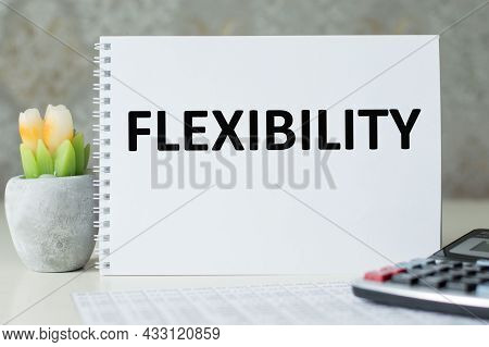 In Notepad, The Text Is Flexibility On The Table Next To A Calculator And A Flower In A Pot