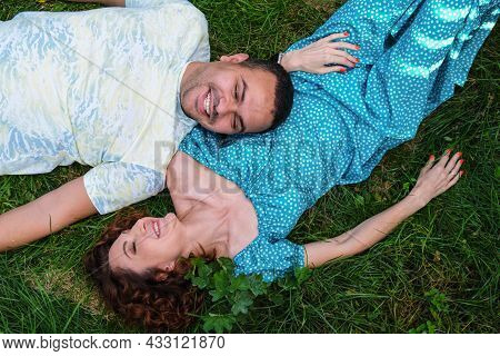Loving Couple Lie On The Grass Look At Each Other And Laugh. Man In A T-shirt And A Curly Woman In A