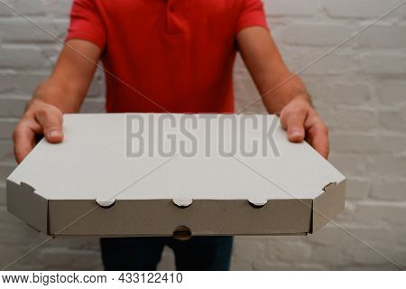 Pizza Delivery. A Courier In A Red Polo Holds A Cardboard Box With Pizza. Food Delivery