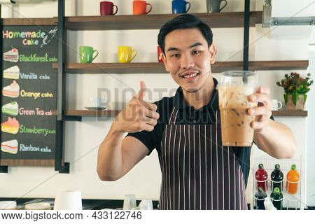 Happy Smiling Asian Man Owner With Apron Making Coffee In  Small Cafe. Professional Barista Preparin