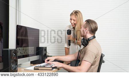 Caucasian Female Singer Holding Mic Singing Fun While Male Sound Engineer Wear Headphones Listen Aud