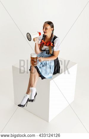 Young Beautiful Woman, Waitress In Traditional Austrian Or Bavarian Costume Sitting With Megaphone O