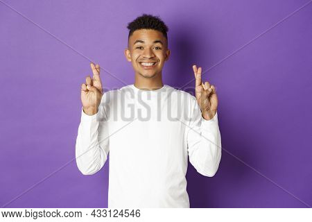 Image Of Handsome African-american Young Guy In White Sweatshirt, Looking Hopeful And Smiling With C